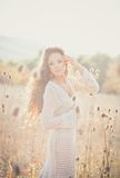 Young woman with beautiful curly hair posing in field at sunset Stock Images