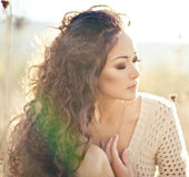 Young woman with beautiful curly hair posing in field at sunset. Young pretty woman with long beautiful curly hair posing in a field at sunset stock image