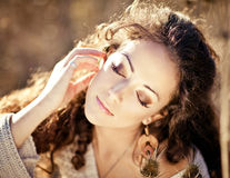 Young woman with beautiful curly hair posing in field at sunset Stock Photos