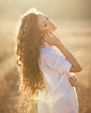 Young woman with beautiful curly hair posing in field at sunset Royalty Free Stock Photo