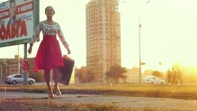 Young woman in beautiful dress with shopping bags goes on the street through the sun spinning around during sunset in stock footage