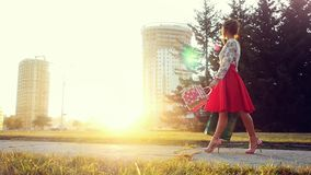 Young woman in beautiful dress with shopping bags goes on the street through the sun during sunset in slowmotion stock video