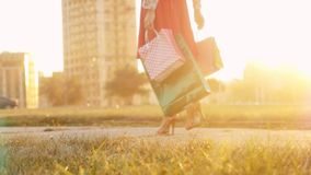 Young woman in beautiful dress with shopping bags goes on the street through the sun during sunset in slowmotion stock video footage
