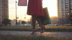 Young woman in beautiful dress with shopping bags goes on the street through the sun during sunset using smartphone in stock video