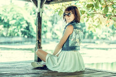 Young woman in beautiful dress and sunglasses posing in gazebo. Tropical island Bali, Indonesia. Portrait of young Royalty Free Stock Images