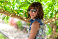 Young woman in beautiful dress and sunglasses posing in gazebo. Tropical island Bali, Indonesia. Portrait of young Royalty Free Stock Image