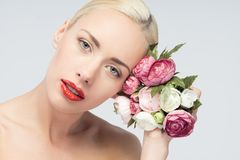 Young woman with beautiful face and flowers. Skin Stock Photo