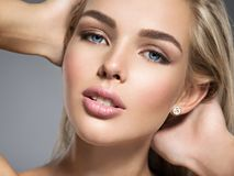 Young Woman with beautiful face. Portrait of  a Young Woman with beautiful face, brown make-up.  Pretty gorgeous girl with  blue eyes -  posing at studio Royalty Free Stock Photo