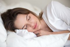 Young woman sleeping well lying asleep in comfortable cozy bed. Young woman with beautiful face sleeping well on white cotton sheets and soft pillow lying asleep stock photos