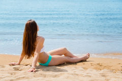 Young woman beautiful girl sitting on beach. Young woman beautiful girl sitting on the beach on a summer day Royalty Free Stock Image