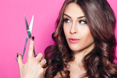 Woman hold scissors. Young woman with beautiful hair look at scissors in one hand studio shot pink background Stock Image
