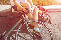 Young woman with beautiful legs sits next to a bicycle blurred Stock Photos