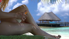 Young woman with beautiful legs uses sunscreen on the tropical beach. Slow motion. Young woman with beautiful legs uses sunscreen on a tropical beach. Slow stock video