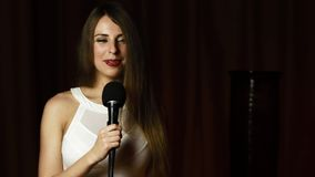 Young woman with beautiful long wavy hair holds mic and sings with radiant smile