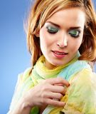 Young woman with beautiful makeup. Closeup portrait of a young woman with beautiful makeup on blue background Royalty Free Stock Images