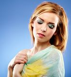 Young woman with beautiful makeup. Closeup portrait of a young woman with beautiful makeup on blue background Royalty Free Stock Photography