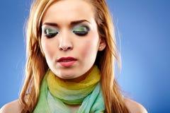 Young woman with beautiful makeup. Closeup portrait of a young woman with beautiful makeup on blue background Stock Photos