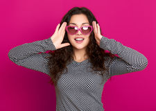 Young woman beautiful portrait, posing on pink background, long curly hair, sunglasses in heart shape, glamour concept Stock Images
