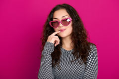 Young woman beautiful portrait, posing on pink background, long curly hair, sunglasses in heart shape, glamour concept Stock Photo