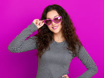 Young woman beautiful portrait, posing on purple background, long curly hair, sunglasses in heart shape, glamour concept Stock Photography