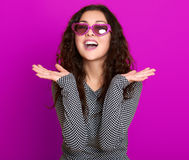 Young woman beautiful portrait, posing on purple background, long curly hair, sunglasses in heart shape, glamour concept Royalty Free Stock Image