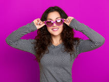 Young woman beautiful portrait, posing on purple background, long curly hair, sunglasses in heart shape, glamour concept Stock Image