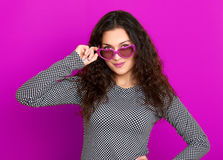 Young woman beautiful portrait, posing on purple background, long curly hair, sunglasses in heart shape, glamour concept Stock Photos