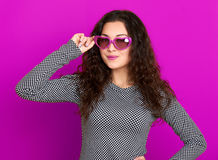 Young woman beautiful portrait, posing on purple background, long curly hair, sunglasses in heart shape, glamour concept Stock Photo