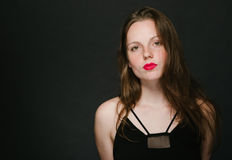 Young woman beautiful portrait with red lips and freckles in classic dress on black baackground Royalty Free Stock Photos