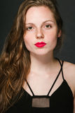 Young woman beautiful portrait with red lips and freckles in classic dress on black baackground Royalty Free Stock Images