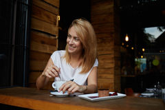 Young woman with beautiful smile looking away while sitting in cafe during coffee break, happy charming hipster girl relaxing in m Royalty Free Stock Photo