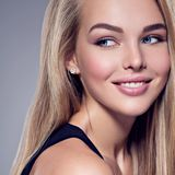Young Woman with beautiful smile. Portrait of  young woman with beautiful smile. Pretty gorgeous girl  with long light straight  hairs and brown make-up.  Face Royalty Free Stock Photography