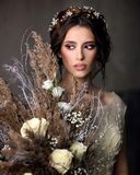 Young woman in a beautiful wedding dress. Portrait of the bride with a bouquet.