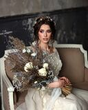 Young woman in a beautiful wedding dress on the sofa. Portrait of the bride with a bouquet.