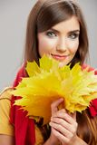 Young woman beauty portrait with yellow autumn leaves. Close up stock photo