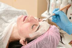 Young woman in beauty salon does make application of moisturizing, softening, regenerating mask. Before the rejuvenating, toning procedure darsonval on the face royalty free stock photos