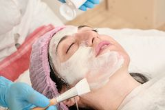 Young woman in beauty salon does make application of moisturizing, softening, regenerating mask. Before the rejuvenating, toning procedure darsonval on the face stock images