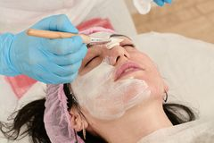 Young woman in beauty salon does make application of moisturizing, softening, regenerating mask. Before the rejuvenating, toning procedure darsonval on the face royalty free stock photography