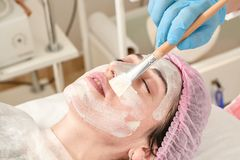 Young woman in beauty salon does make application of moisturizing, softening, regenerating mask. Before the rejuvenating, toning procedure darsonval on the face stock photos