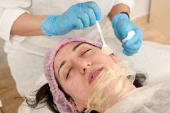 Young woman in beauty salon does skin moisturizing procedure after ultrasound peeling. And facial cleansing procedure. Ultrasound procedure. Medical and beauty stock photos