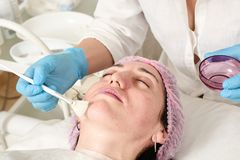 Young woman in beauty salon does skin moisturizing procedure after ultrasound peeling. And facial cleansing procedure. Ultrasound procedure. Medical and beauty stock image