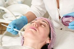 Young woman in beauty salon does skin moisturizing procedure after ultrasound peeling. And facial cleansing procedure. Ultrasound procedure. Medical and beauty royalty free stock images