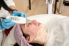 Young woman in beauty salon does ultrasound peeling and facial cleansing procedure. Cosmetic multifunctional device. Ultrasound procedure. Medical equipment royalty free stock photography