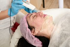 Young woman in beauty salon does ultrasound peeling and facial cleansing procedure. Cosmetic multifunctional device. Ultrasound procedure. Medical equipment stock image