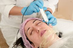 Young woman in beauty salon does ultrasound peeling and facial cleansing procedure. Cosmetic multifunctional device. Ultrasound procedure. Medical equipment royalty free stock images