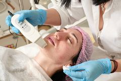 Young woman in beauty salon does ultrasound peeling and facial cleansing procedure. Cosmetic multifunctional device. Ultrasound procedure. Medical equipment stock photography