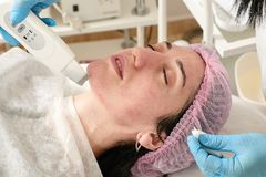 Young woman in beauty salon does ultrasound peeling and facial cleansing procedure. Cosmetic multifunctional device. Ultrasound procedure. Medical equipment royalty free stock photos