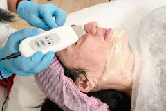 Young woman in beauty salon does ultrasound peeling and facial cleansing procedure. Cosmetic multifunctional device. Ultrasound procedure. Medical equipment royalty free stock photo