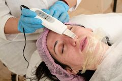 Young woman in beauty salon does ultrasound peeling and facial cleansing procedure. Cosmetic multifunctional device. Ultrasound procedure. Medical equipment royalty free stock image