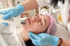 Young woman in beauty salon does ultrasound peeling and facial cleansing procedure. Cosmetic multifunctional device. Ultrasound procedure. Medical equipment stock photos